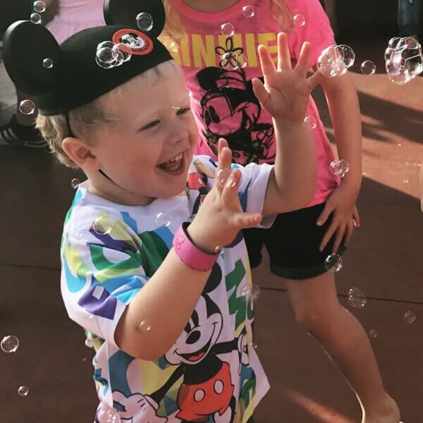 a young boy plays with bubbles at Walt Disney World, wearing a Mickey ear hat. Photograph of pure joy at Disney Parks