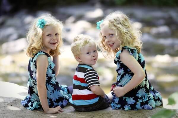 Three young children pose for a portrait session