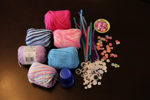 yarn, pipe cleaners, google eyes, and craft supplies for little love bug valentines day crafts