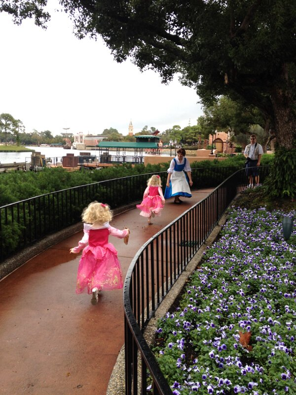 two little girls dressed as princess run through Epcot with Belle