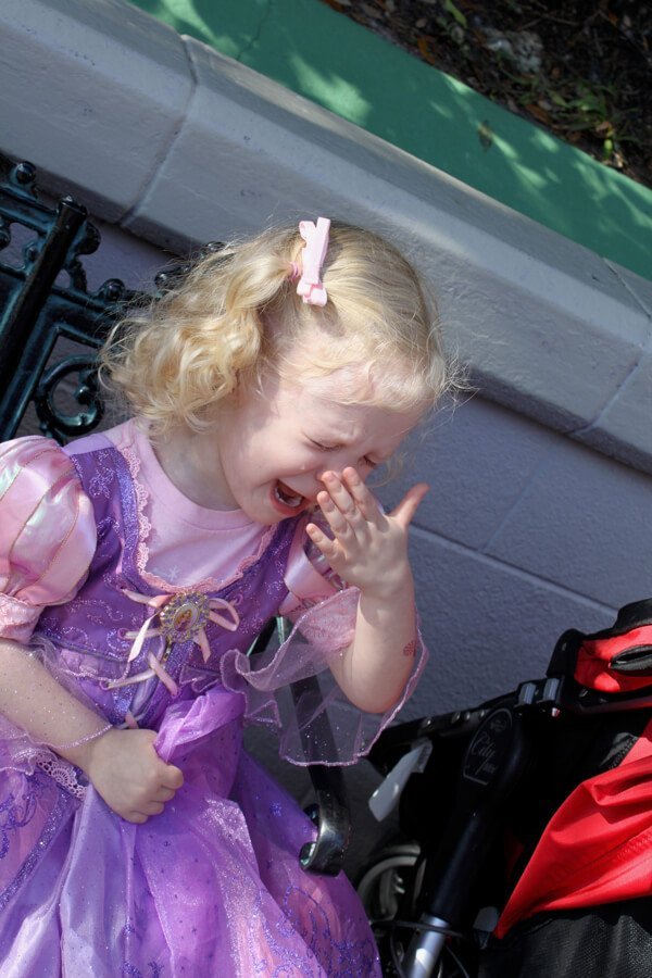 A toddler girl in a princess dress, crying at Walt Disney World