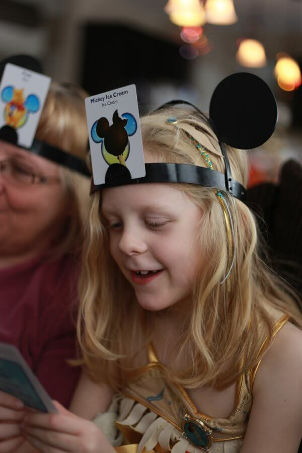 Family playing hedbanz game, which is similar to 20 questions - and excellent option for your arsenal of road trip games