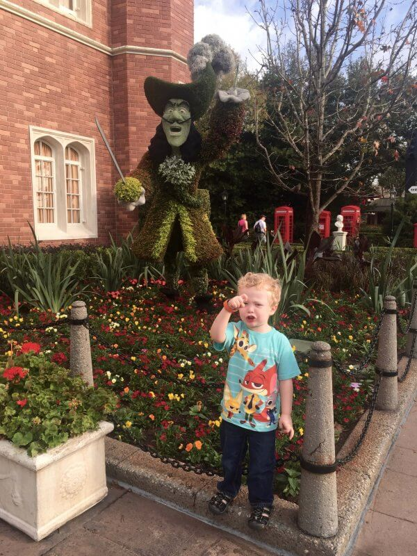 boy stands with captain hook topiary at Epcot's Flower & Garden Festival and outdoor kitchens