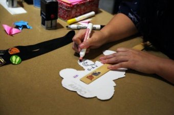 At Epcot's Kidcot Stations, cast members draw a picture and write in Japanese on a Duffy puppet