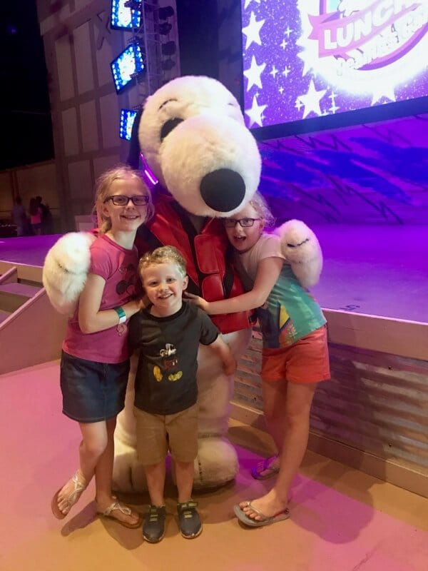 "Three kids hug snoopy at Kings Island's show ""Lunch with the Peanuts Gang"""