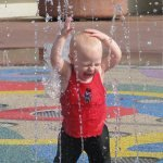 young child plays in a fountain at epcot
