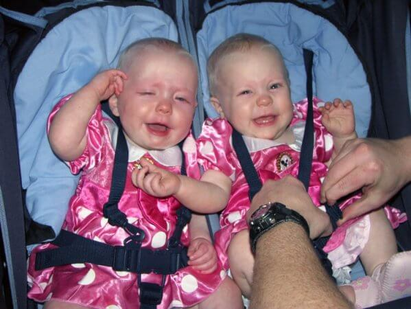 Two tired babies cry in a stroller on a long day of travel