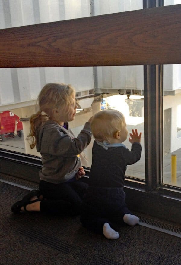 Toddler and Preschooler watch a plane at the airport