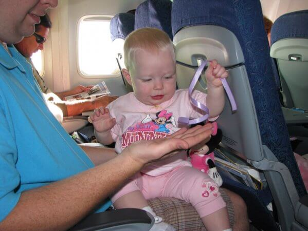 toddler playing with ribbon on a plane, to keep her entertained during long travel days