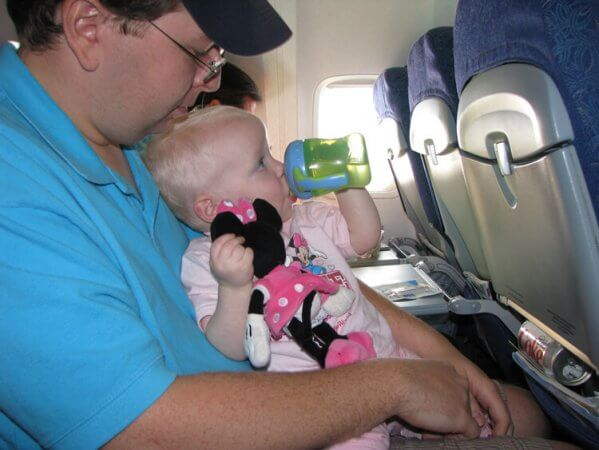 Toddler sips from a cup during airplane takeoff to relieve thirst and ear pressure