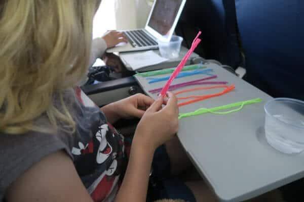 Child plays with Wikki Stix on a plane