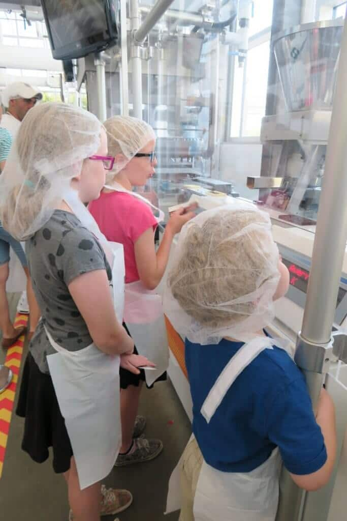 "3 kids watching the factory line at Hershey's Chocolate World ""Create Your Own Candy Bar"" experience"