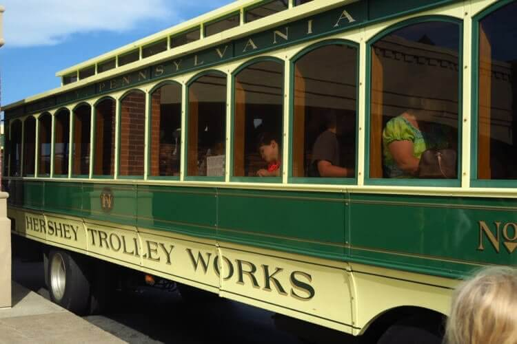 "Green and Yellow ""Trolley Works"" trolley at Hershey Chocolate World, boarding for a seasonal tour around Hershey, Pennsylvania"