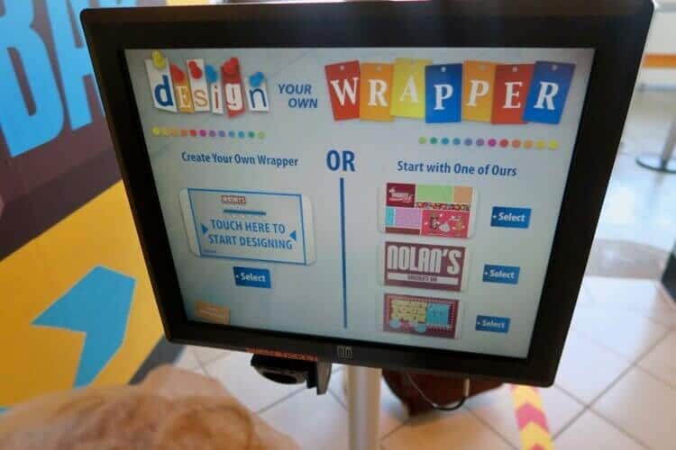 "An interactive screen in the Hershey's Chocolate World ""Create Your Own Chocolate Bar"" experience, showing wrapper design options"