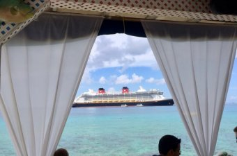 A view of the Disney Fantasy out of a window with sheer curtains, taken from the Paradise restaurant in Grand Cayman