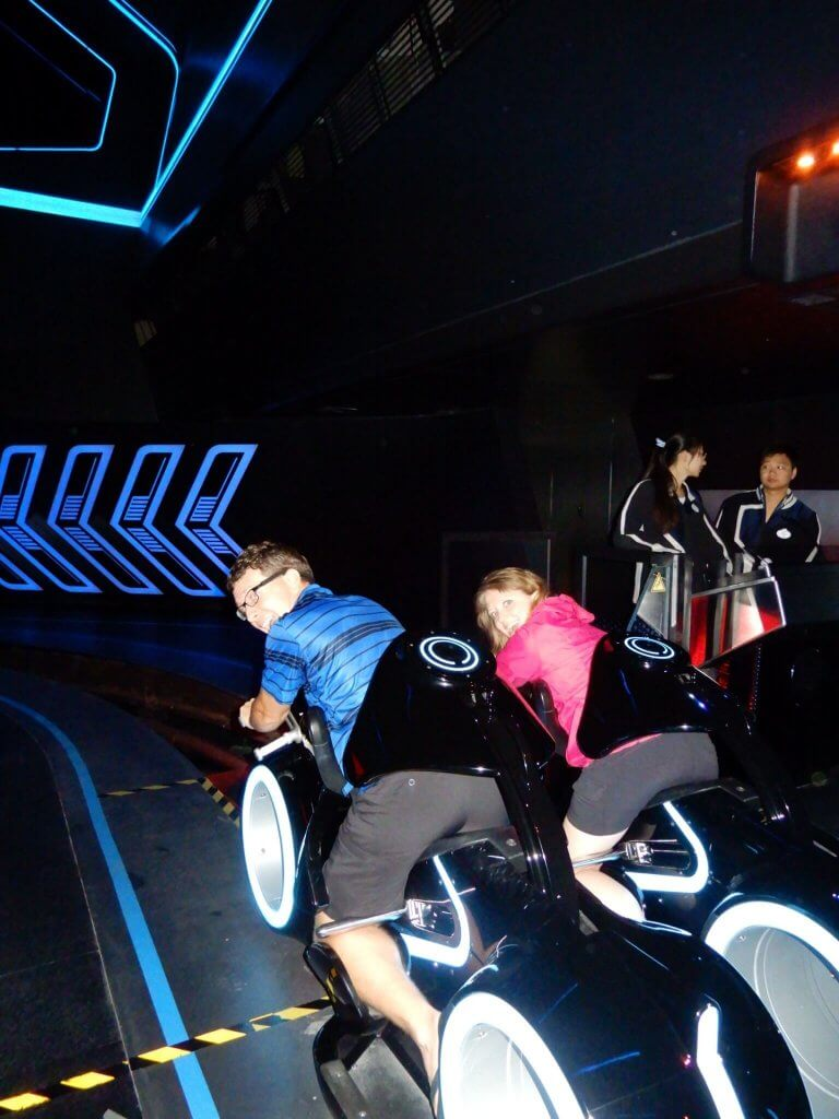 two adults riding on the Tron Lightcycle Power Run motorcycle style vehicle attractions