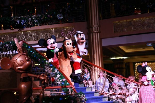 Mickey, Pluto, and Goofy, dressed for Christmas and walking down steps in a Disney Cruise ship atrium