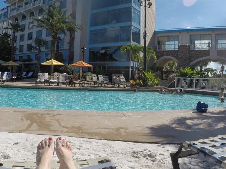 guest sits at white sand beach and pool area at Loews Sapphire Falls Resort in Orlando