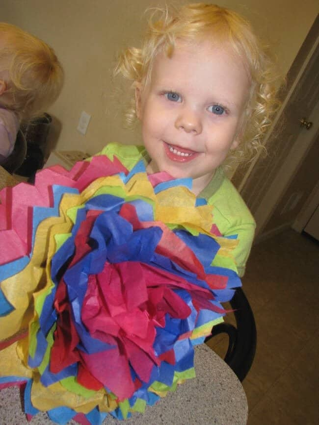 preschooler holds a tissue paper flower for a mexican themed party