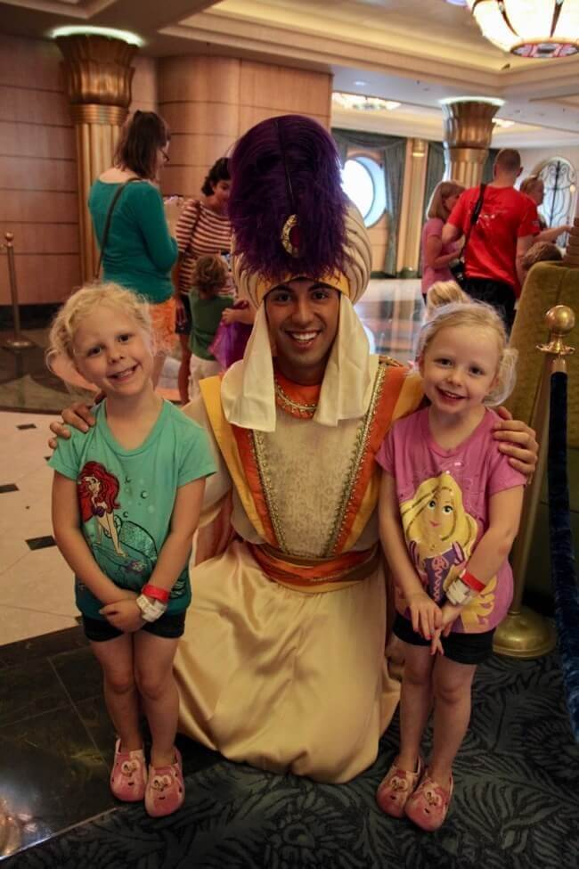 Two preschool girls meet Prince Ali on the Disney Fantasy during one of several character meet and greets in the atrium