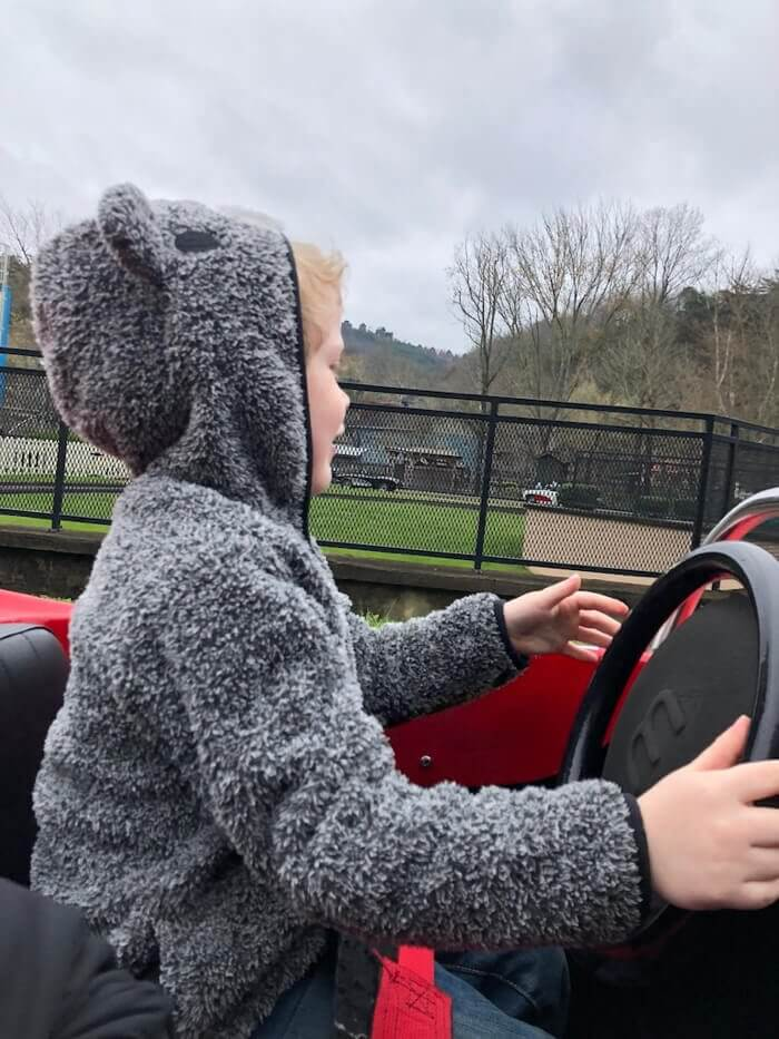 a young boy drives a car in the Rockin' Roadway attraction at Pigeon Forge's Dollywood theme park