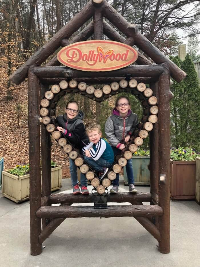 three kids pose in a wooden heart shaped sign in Dollywood, on a family vacation to Pigeon Forge, TN