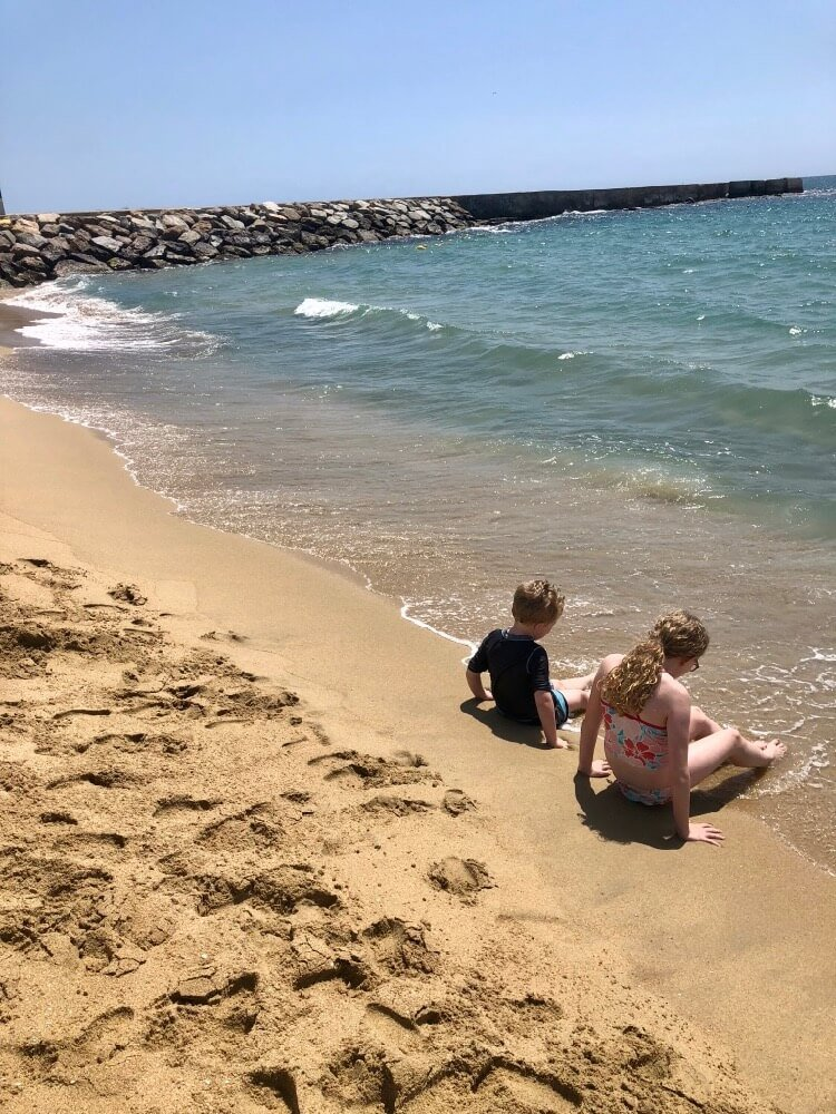 two kids sitting on Nova Icaria, a family-friendly beach in Barcelona, Spain (near La Rambla)