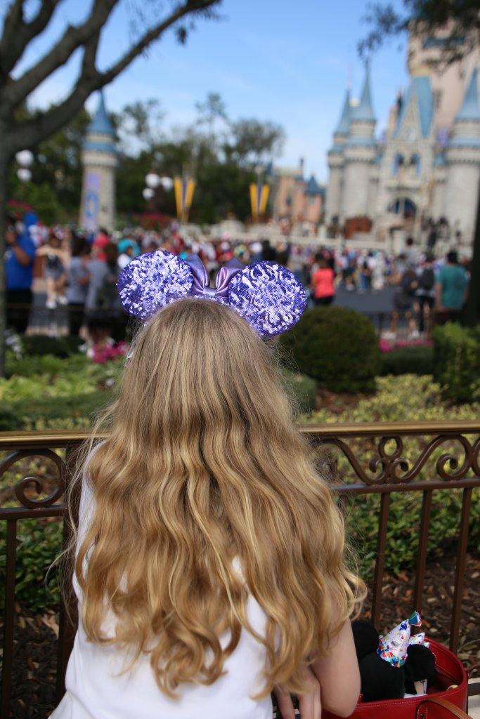 a girl watching a stage show at Cinderella Castle, wearing a potion purple Minnie Mouse headband