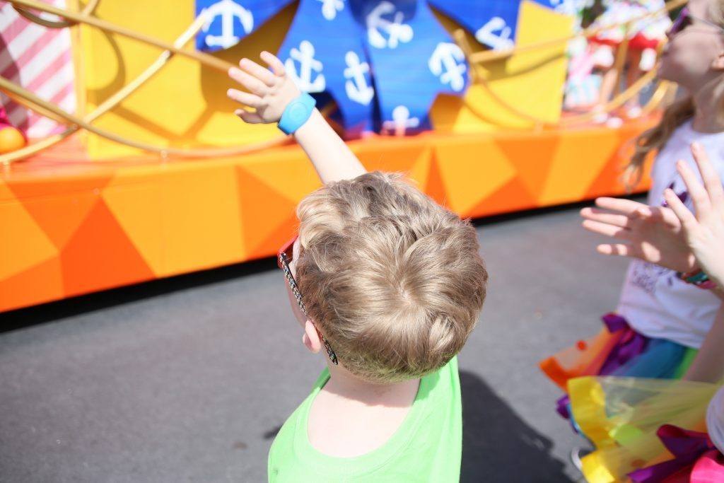 child waving at a Move it shake it mousekedance it street party float in Walt disney world