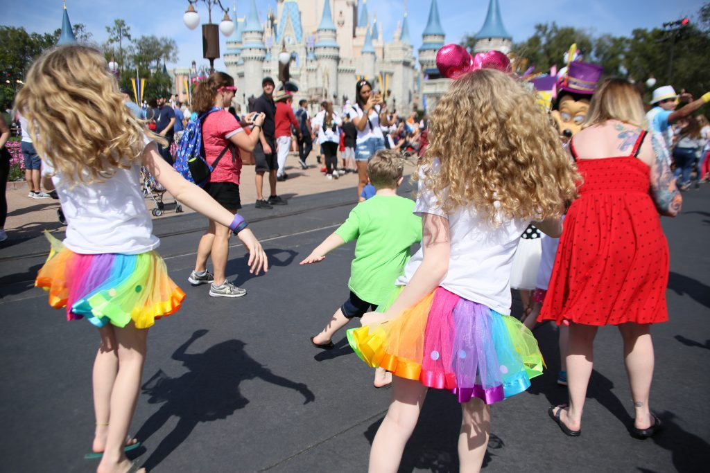 children dancing in the street in front of cinderella castle during Walt disney world's Move It Shake It Mouskedance It Street Party
