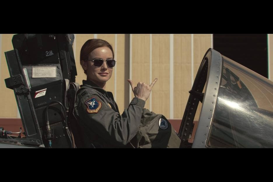carol danvers/captain marvel in a flight suit sitting in the cockpit of a plane with aviator glasses