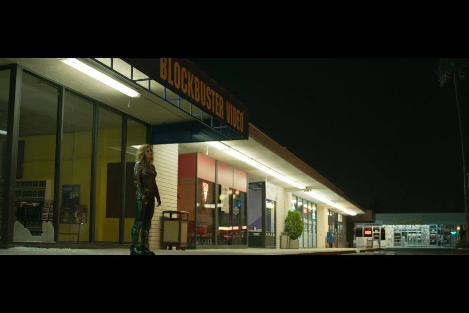 carol danvers / captain marvel standing outside a blockbuster video, one of many 1990s references or Easter eggs Marvel's captain marvel