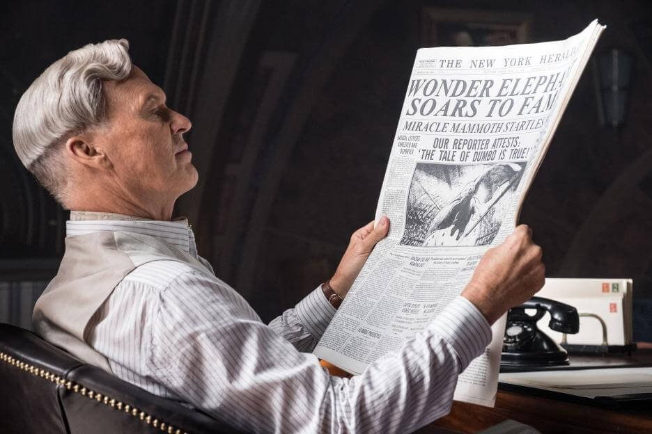 Michael Keaton reading a newspaper as the villain in Tim burton's 2019 dumbo