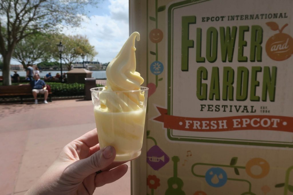 dole whip at Epcot held up before a Flower and Garden festival sign
