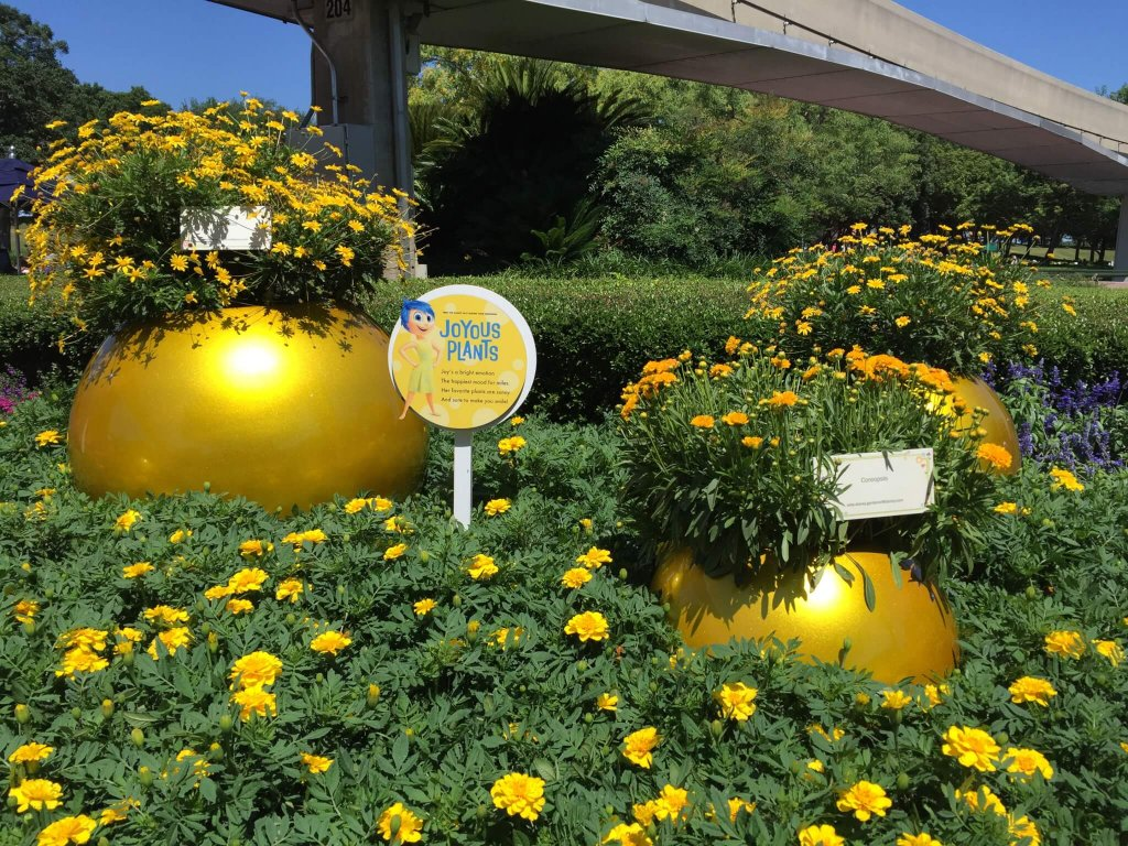 """joyful plants"" sign with Joy from Pixar's Inside Out, next to yellow flowers at Epcot's flower & garden festival"