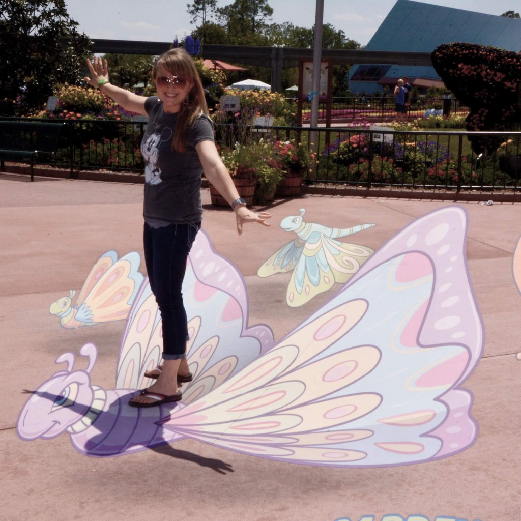 woman standing on a chalk butterfly drawing at during the Food and Wine Festival at Epcot in the spring