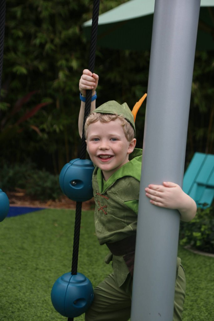 young boy In a Peter Pan costume playing on a playground at Walt disney world Epcot festival of the arts or flower and garden festival