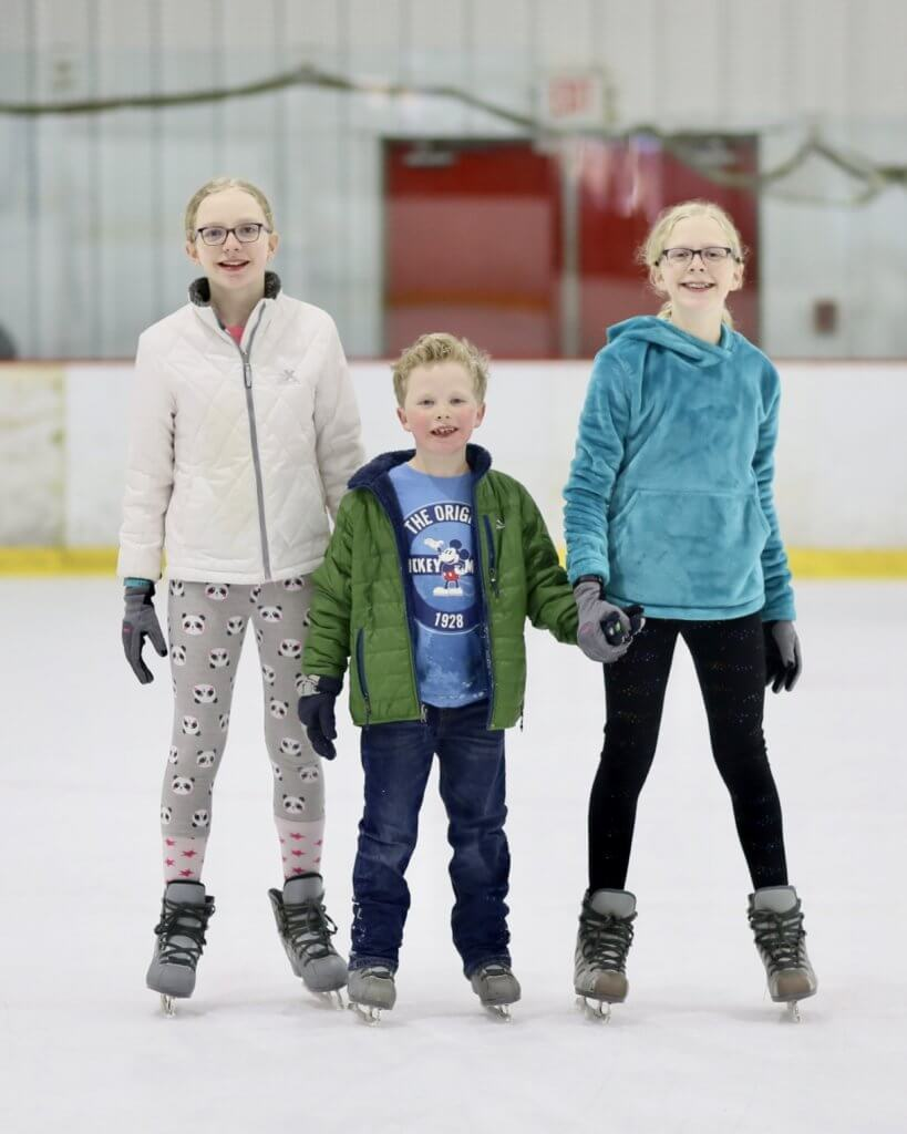 three kids stand on ice skating rink to celebrate the release of Frozen 2 on Blu-ray and digital