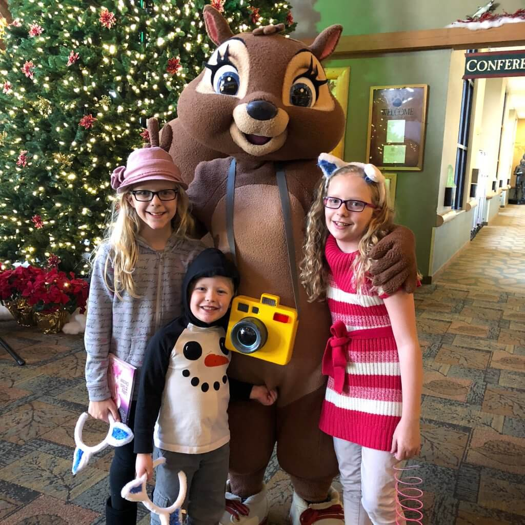 three kids stand posed with a squirrel character in costume at Great Wolf Lodge. the squirrel has a yellow camera around her neck