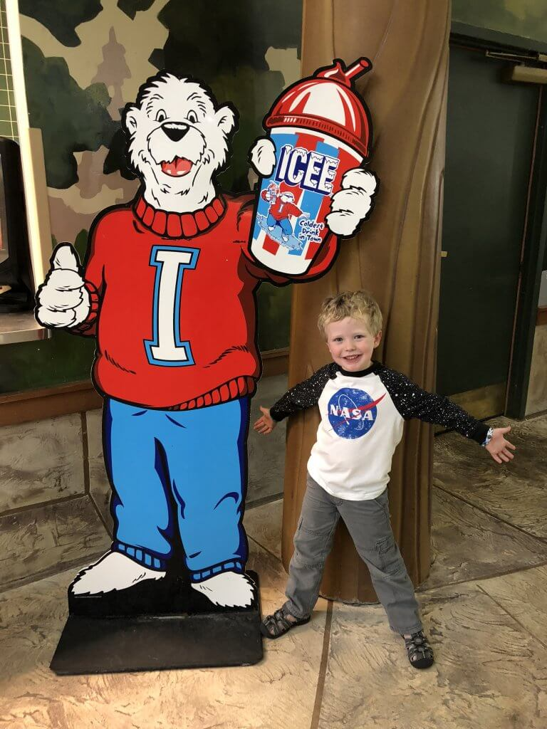 small boy posing next to Icee bear signage