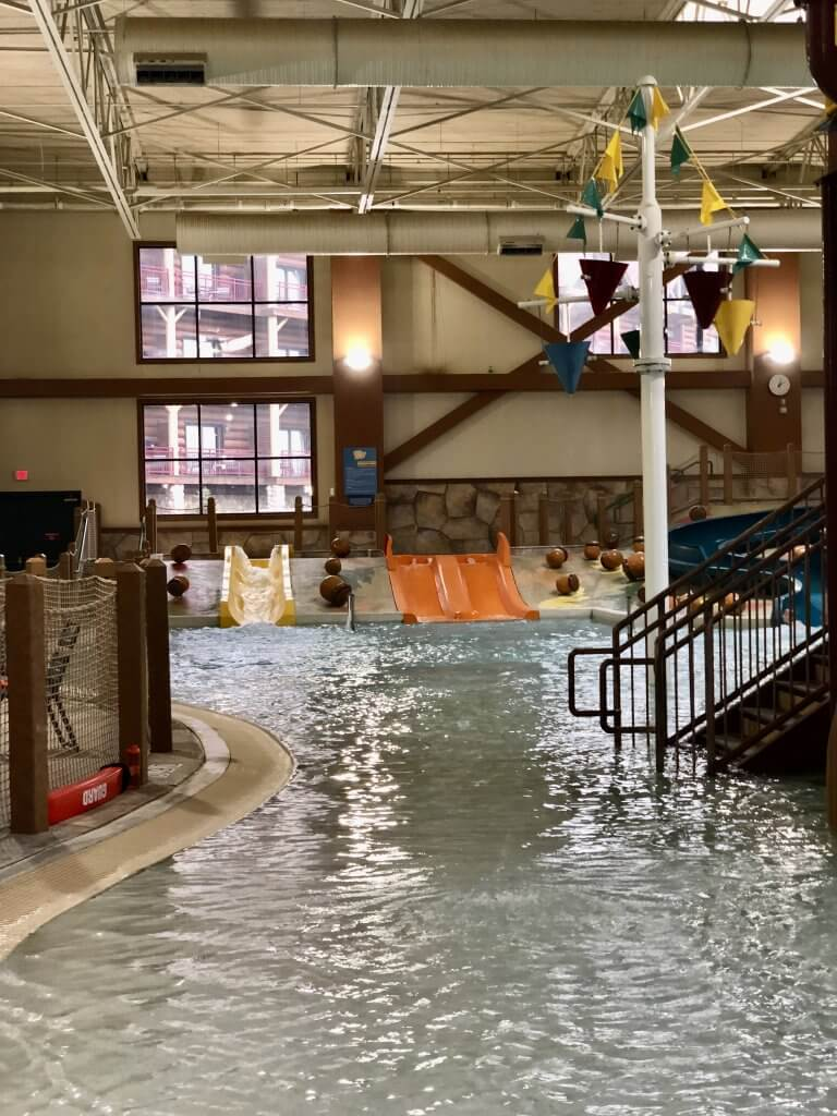 toddler-friendly play area inside Great Wolf Lodge waterpark including small water slides in the background and zero entry/shallow water in the foreground