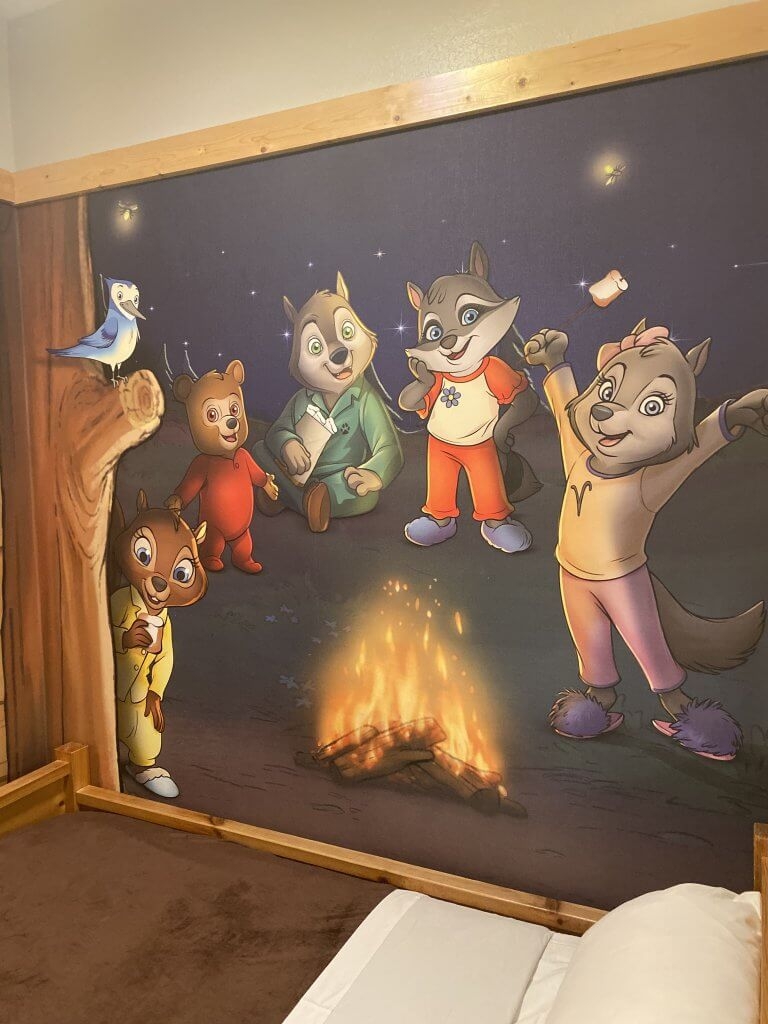 squirrel, bear, raccoon, and other woodland creatures painted on a mural in the kids cabin space of a Great Wolf Lodge themed suite