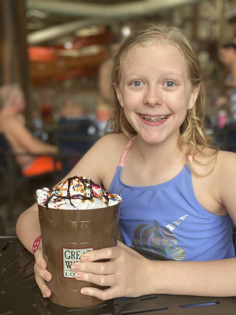 "a young girl shows a Great Wolf Lodge ""tipping bucket"" ice cream sundae from the Buckets counter service restaurant inside the waterpark"